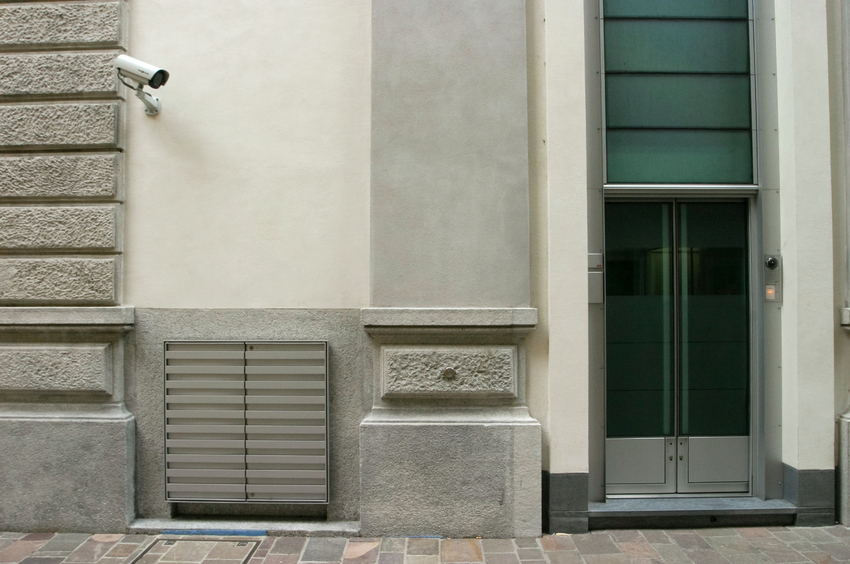 front of modern bank entrance with surveillance security system.